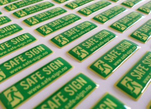 white foil + doming gel, printed CMYK or PMS with cut to shape rectangle with round corners (1.5-2 mm). Size: 3.0 x 1.0 cm
