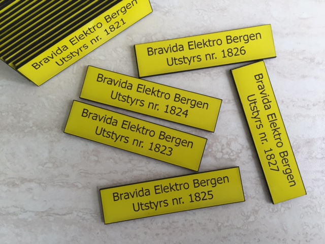 1.5 mm double-layer ABS, yellow color on front and black on other sides. Laser engraved, cut to size 8 x 2 cm with double-tape on back for indoor wall mounting