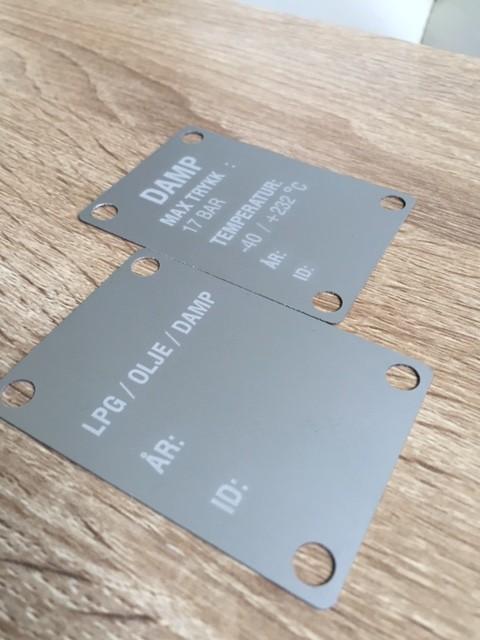 0.5 mm anodized matt silver aluminium, engraving in white, 0.5 mm holes Size: 7 x 5 cm