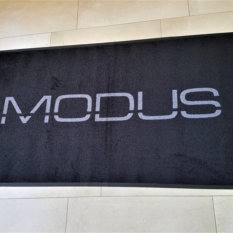 100% High Twist Nylon, Polyamid 6.6, backing - 100% Nitrile rubber; grey logo on black background. Size: 100 x 180 cm