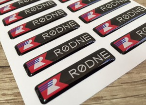 white foil + doming gel, printed CMYK or PMS with cut to shape rectangle with round corners (1.5-2 mm). Size: 4.0 x 1.0 cm