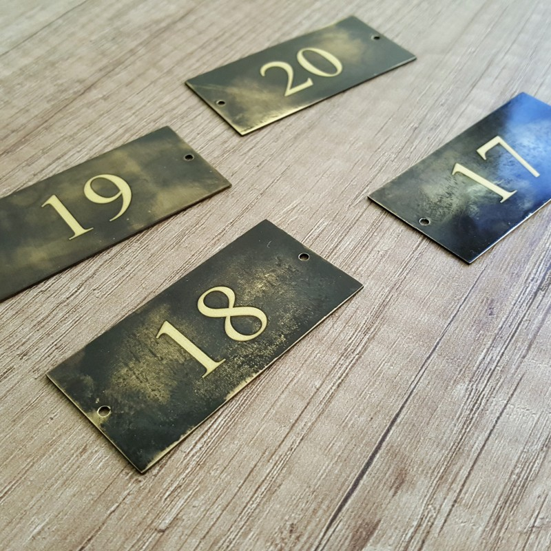 Artificially aged brass with engraved numbers, 2 holes. Size: 6 x 3 cm