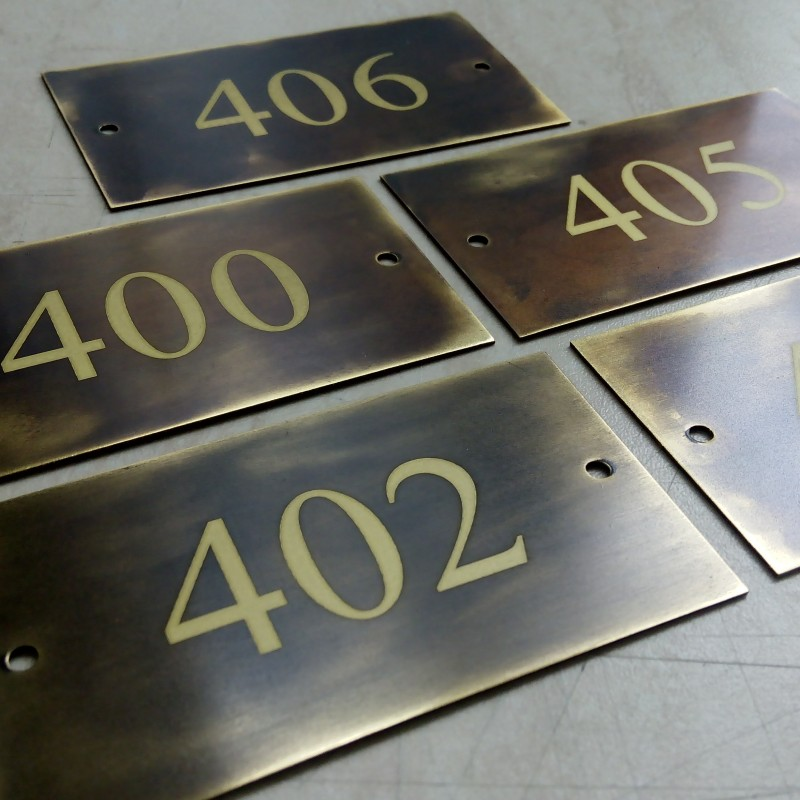 Artificially aged brass with engraved numbers, 2 holes.