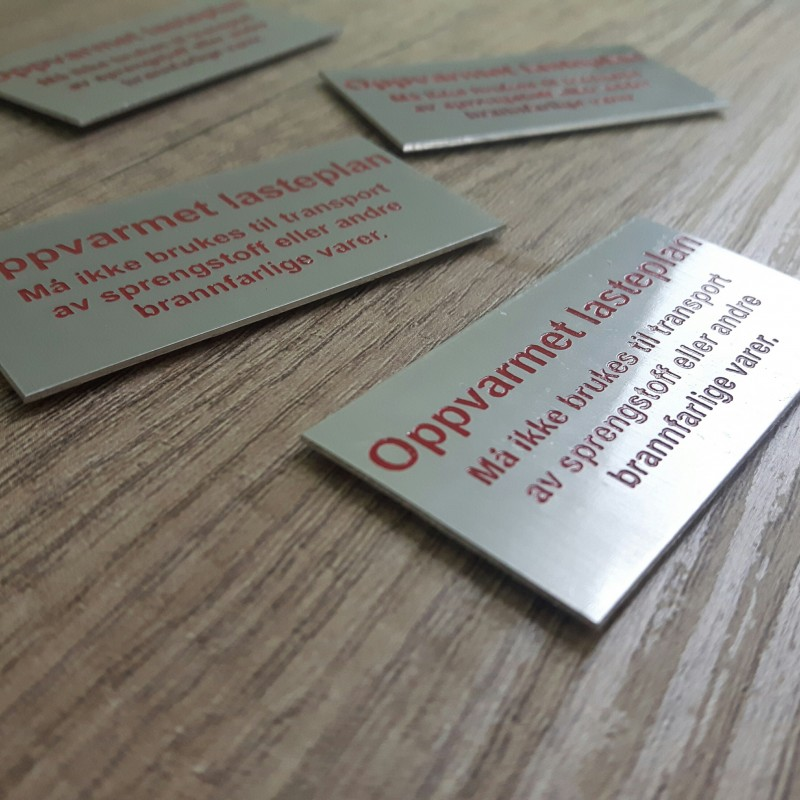 1 mm aluminium, engraved and painted in red paint logo, varnishing, double tape on the back. Size: 6 x 3 cm