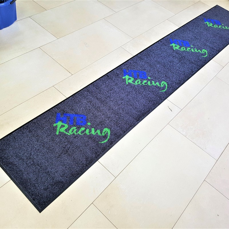 100% High Twist Nylon, Polyamid 6.6, backing - 100% Nitrile rubber, blue and green logo on black background. Size: 0.5 x 3.2 m